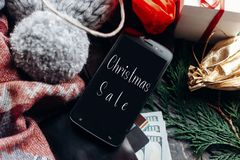 Christmas big sale. special christmas offer discount text on pho. Ne screen message on seasonal rustic background with money cards wallet and bag with stuff and Stock Photography
