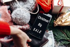 Christmas big sale. special christmas offer discount text on pho. Ne screen message on seasonal rustic background with money cards wallet and bag with stuff and Stock Image