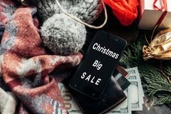 Christmas big sale. special christmas offer discount text on phone screen message on seasonal rustic background with money cards. Wallet and bag with stuff and stock images
