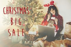 Christmas big sale text. Holiday discount offer. Girl in reindeer antlers holding credit card and shopping on phone, sitting with. Laptop at golden beautiful stock photography