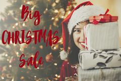 Christmas big sale text. Holiday discount offer. Happy girl in s. Anta hat holding many gift boxes at golden beautiful christmas tree with lights in festive room stock photos