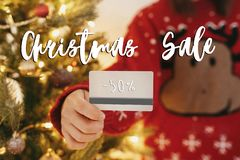 Christmas big sale text. 50 percent Holiday discount offer. Woman holding credit card on background of golden beautiful christmas. Tree with lights in festive stock photo