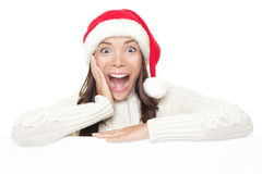 Christmas billboard woman surprised sign. Billboard woman in santa hat leaning on banner for Christmas. Surprised asian beautiful happy model showing blank sign royalty free stock photos