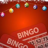 Christmas bingo baubles on festive red background. Festive Decorated Red Background Copy Space with Snow Christmas Bingo Lottery Baubles and Bingo Cards Royalty Free Stock Photos