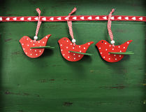 Christmas bird decorations on vintage green wood background. Christmas holiday background with red, white, festive polka dot birds against a vintage style dark Stock Images