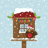 Christmas birdhouse. Decorated birdhouse with perched christmas robin redbreast Royalty Free Stock Photography