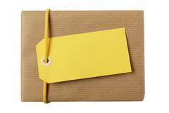 Christmas or birthday present with blank yellow gift tag. Christmas or birthday gift wrapped in eco friendly paper with white decoration ribbon and blank white Stock Photo