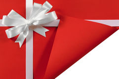 Christmas or birthday white satin gift ribbon bow on red pap Royalty Free Stock Images