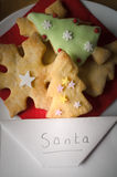 Christmas Biscuits with Envelope Addressed to Santa. Christmas concept.  Overhead of a plate of shaped Christmas biscuits (cookies)  with an envelope addressed Stock Photo