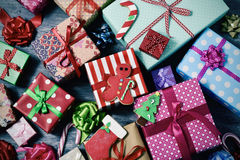 Christmas biscuits and gifts. High-angle shot of some christmas cookies and a pile of gifts wrapped in nice papers and tied with ribbons of different colors on a Royalty Free Stock Photography