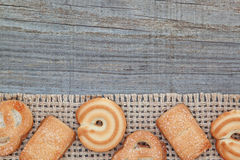 Christmas biscuits on sacking texture and wood. Royalty Free Stock Photos