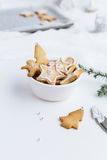 Christmas Biscuits in White Bowl Decorated with Icing and Silver Balls on White Table Royalty Free Stock Photography