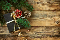 Christmas black gift box with gold ribbon. Pine cones, branches spruce, on wooden planks Royalty Free Stock Photo