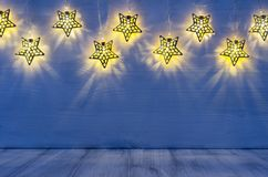 Christmas blank interior with glow lights yellow stars on indigo blue wood background. Royalty Free Stock Photo