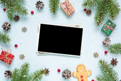 Christmas blank photo card in frame made of fir tree branches, decorations and gift boxes Stock Images