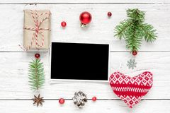 Christmas blank photo card in frame made of fir tree branches, decorations and gift boxes Stock Photos