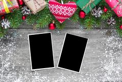 Christmas blank photo frames with fir tree branches, decorations, gift boxes and knitted heart. Over rustic wooden background. mock up. flat lay. top view Royalty Free Stock Photography