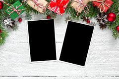 Christmas blank photo frames with fir tree branches, decorations and gift boxes over white wooden background