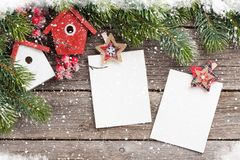 Christmas blank photo frames and fir tree. Christmas blank photo frames, birdhouse decor and snow fir tree on wooden table. Top view with space for your Royalty Free Stock Images