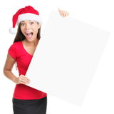 Christmas blank sign woman. Billboard woman in santa hat surprised for Christmas. Surprised asian beautiful happy model showing blank sign isolated on white royalty free stock photography