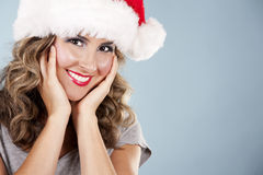 Christmas blond woman. Pretty blond wearing christmas hat on light blue background Royalty Free Stock Photos