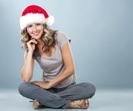 Christmas blond woman. Pretty blond wearing christmas hat on light blue background Royalty Free Stock Image