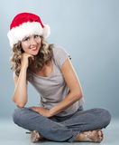 Christmas blond woman. Pretty blond wearing christmas hat on light blue background Stock Photos