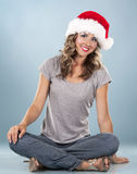 Christmas blond woman. Pretty blond wearing christmas hat on light blue background Royalty Free Stock Photo