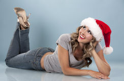 Christmas blond woman. Pretty blond wearing christmas hat on light blue background Stock Photography