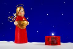 Christmas blue. Christmas angel and candle under snow (blue background and snow added in post stock photography