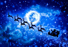 Christmas blue background. Silhouette of Santa Claus flying on a. Christmas background. Beautiful winter with background of snowy night sky, stars and full moon Royalty Free Stock Photo