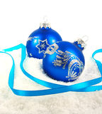 Christmas blue baubles and ribbon on snow Stock Image