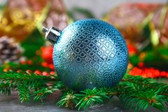 Christmas blue decorative balloon surrounded by fir branches. royalty free stock images