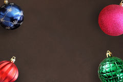 Christmas blue, pink, red wavy and green ribbed ball on dark wooden table Stock Photo