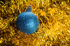 Christmas blue tree toy on a gold tinsel background. For holidays design Royalty Free Stock Photos