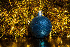 Christmas blue tree toy and tinsel on a gold  background. For holidays design Stock Image