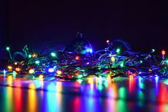 Christmas blurred lights on black background with copy space. Abstract colorful reflections of bulbs on a Christmas tree. Stock Image