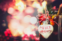Christmas bokeh background with glass of mulled wine or punch with heart and inscription Merry Christmas Royalty Free Stock Photography