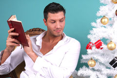 Christmas book reading. Man reading book of christmas stock images