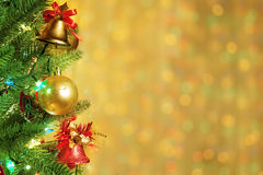 Christmas Border Background. Decorated Christmas tree with bells and ornaments. Lights are sparkling in this frame or border on golden holiday background Royalty Free Stock Image