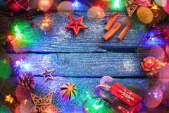 Christmas border with balls, stars and decoration on blue wooden background. Studio shot Stock Images
