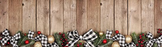 Free Christmas Border Banner With White And Black Checked Buffalo Plaid Ribbon, Ornaments And Branches, Above View On A Wood Background Stock Images - 163888194