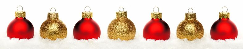 Christmas border of baubles in snow isolated Stock Images