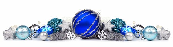 Christmas border of blue and silver ornaments over white. Christmas border of blue and silver ornaments on a white background stock images