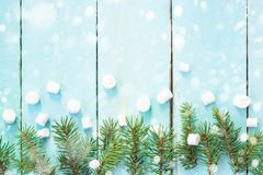 Christmas border with branch of fir tree and marshmallows on wooden background decorated with snow. Top view copy space stock image