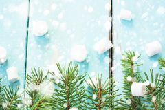 Christmas border with branch of fir tree and marshmallows on wooden background decorated with snow. Top view copy space stock photo
