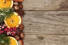 Christmas border with branches, nuts and orange slices on wood Royalty Free Stock Photo