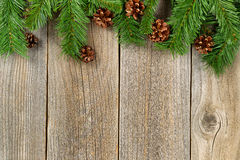 Christmas border with branches and pinecones on rustic wooden bo Stock Images