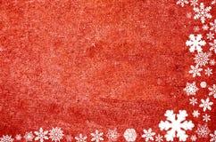 Christmas border composed of snow flakes. Christmas border on red granite wall Royalty Free Stock Image