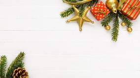 Christmas border composition made of fir branches red gold gift boxes and gold ribbon. On white wooden planks table. Flat lay, top view, copy space royalty free stock images